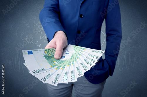 Leinwandbild Motiv Young businessman holding large amount of bills with grungy background
