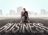 Young determined businessman kneeling before business text  - 223629752
