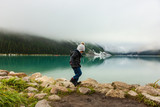 Little boy running around Lake Louise on a foggy day - 223655371