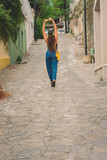 Traveling smiling girl, visit colorful town. she walks through picturesque streets in an attitude of freedom. lifestyle photography