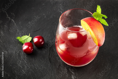 A photo of a vibrant red drink with cherries on black with copy space