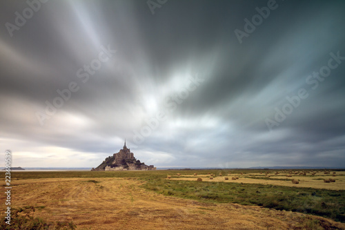 Beautiful view of historic landmark Le Mont Saint-Michel in Normandy, France, a famous UNESCO world heritage site and tourist attraction, long exposure with ominous clouds - 223690539