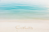 The Word Calm Written in the Sand on a Beach with blue sea background - 223691110