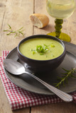 leek cream soup in a dark bowl on a plate, wine, bread and spoon on a rustic wooden table, vertical - 223696764