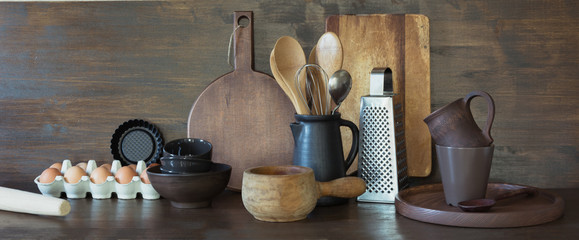 Crockery, clayware, dark utensils and other different stuff on wooden tabletop. Kitchen still life as background for design. Copy space. © svetlana_cherruty