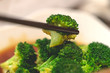 Chopstick picking up Chinese style fried broccoli