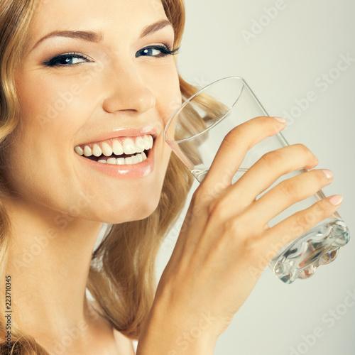 Młoda szczęśliwa kobieta woda pitna, nad szarość