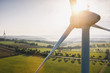 Leinwanddruck Bild - Wind turbine and agricultural fields on a summer day - Energy Production with clean and Renewable Energy - aerial shot