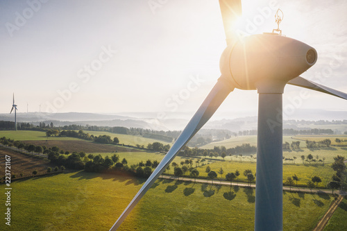 Leinwanddruck Bild Wind turbine and agricultural fields on a summer day - Energy Production with clean and Renewable Energy - aerial shot