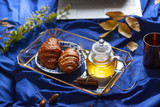 Breakfast in bed concept close up with croissants and a glass pot of green tea  - 223723178