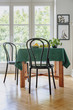 Quadro Black chair next to a table with green cloth in a dining room interior. Balcony window in the background. Real photo