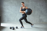 Woman In Stylish Sports Wear Training With Med Ball - 223731959