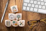 Symbole für Cloud Services auf Würfeln am Arbeitsplatz