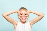 funny ludicrous joyful comic playful girl pretending to look through binoculars made of hands. portrait of a kid on blue background. emotion facial expression concept. - 223748151