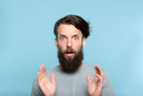 omg unbelievable shock amazement. dumbfounded man with open mouth. portrait of a young bearded guy on blue background. emotion facial expression and reaction concept. - 223748552