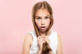 haircare and styling for kids. beauty and health. quality shampoo and conditioner products or hair salon for children. adolescent girl with locks in her hands on pink background.