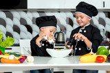 A family of cooks.Healthy eating.Children prepares vegetable salad in kitchen. - 223755176