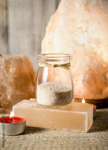 Himalajska sól groszkuje w ślicznym round szklanym słoju na drewnianym tle. Blokuje sól używaną do serwowania potraw.