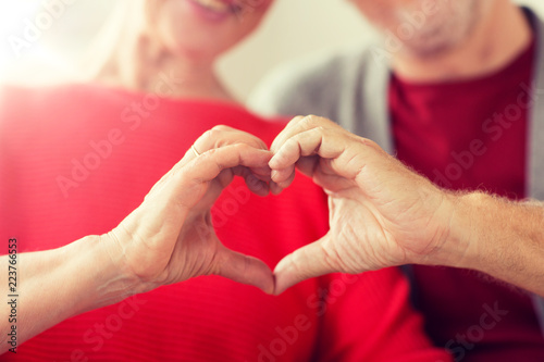 relationships, love and old people concept - close up of senior couple showing hand heart gesture - 223766553
