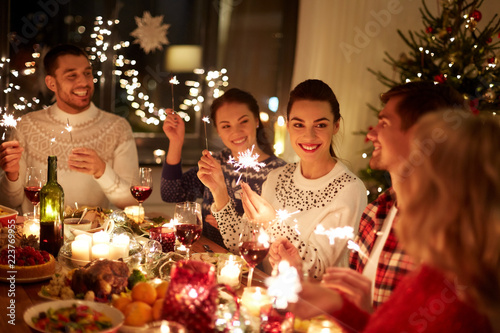winter holidays and people concept - happy friends with sparklers celebrating christmas at home feast - 223769955
