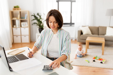 multi-tasking, freelance and motherhood concept - working mother with laptop computer counting on calculator and baby boy playing at home office