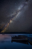 Vibrant Milky Way composite image over landscape of still lake with boats on jetty - 223792354