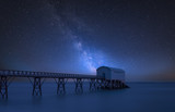 Vibrant Milky Way composite image over landscape of long exposure image of lifeboat jetty at sea - 223792357