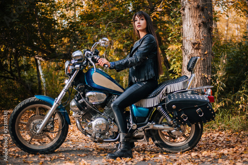 Girl on a motorcycle in a black jacket and leather pants. Women biker