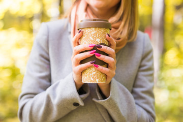 Autumn, nature and people concept - Close up of woman in grey coat holding a cup of coffee