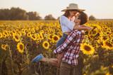 loving couple is walking in a blooming sunflower field - 223832139