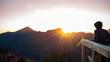 Leinwandbild Motiv Young person in a raincape watching the sunrise in the mountains