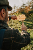 scientist examines leaf of tree through magnifying glass - 223838950