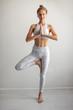 Leinwanddruck Bild - Tan skin caucasian woman wearing white elastic sports clothes meditating in yoga tree pose at studio white background. Healthy lifestyle, Yoga fitness concept.