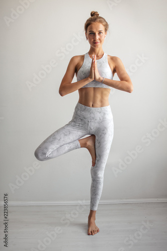 Fototapeta Tan skin caucasian woman wearing white elastic sports clothes meditating in yoga tree pose at studio white background. Healthy lifestyle, Yoga fitness concept.