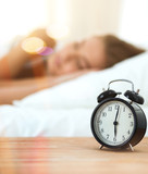 Young sleeping woman and alarm clock in bedroom at home - 223859587