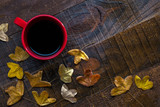 Red cup of  black coffee and  autumn leaves on  old  wet wooden table.  Flat lay - 223859722