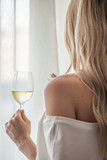 Rear view of a blond woman holding glass of wine and looking through window - 223867177