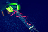 green headphone with red audio cable on acoustic guitar, focus on connector. music background