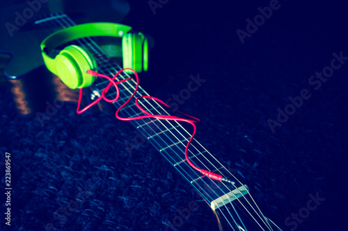 green headphone with red audio cable on acoustic guitar, focus on connector. music background - 223869547