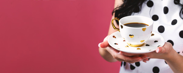 Young woman holding a cup of coffee on a solid background © Tierney