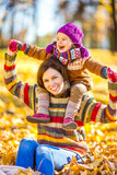 Little girl playing with mother in the autumn park - 223893912