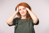Fashion and people concept - young woman hide ran her hands in red head and smile