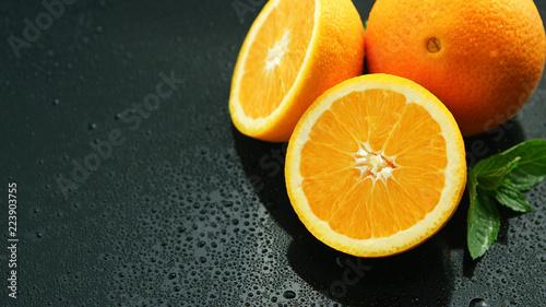 Od above zbliżenia strzału pokrojona i cała pomarańcze z zielonym liściem na mokrym ciemnym stole