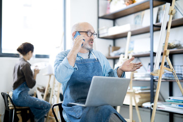 Mature bearded man in apron sitting in front of easel in workshop and talking to someone on smartphone