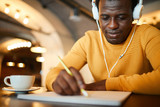 Young serious man with headphones looking at blank paper in front of him while learning to draw professionally