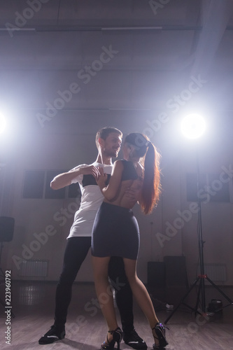 Young couple dancing latin dance Bachata, merengue, salsa. Two elegance pose in dance class - 223960792
