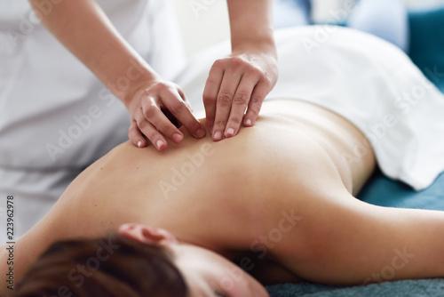 Młoda kobieta odbiera masaż pleców przez profesjonalnego terapeuty.
