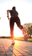 Young attractive sporty fitness woman running while exercising outdoors at sunset or sunrise.