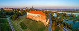 Wide aerial panorama of Sandomierz old city, Poland, in sunset light, with medieval gothic castle in front, old town, gothic cathedral, and the Vistula river with a bridge in the background