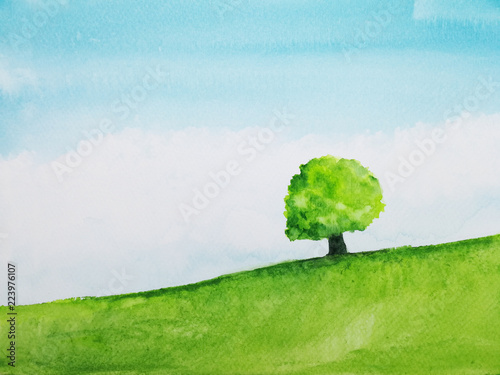 watercolor  landscape hill and tree stand alone in green meadow field with blue sky.hand drawn on paper. © atichat